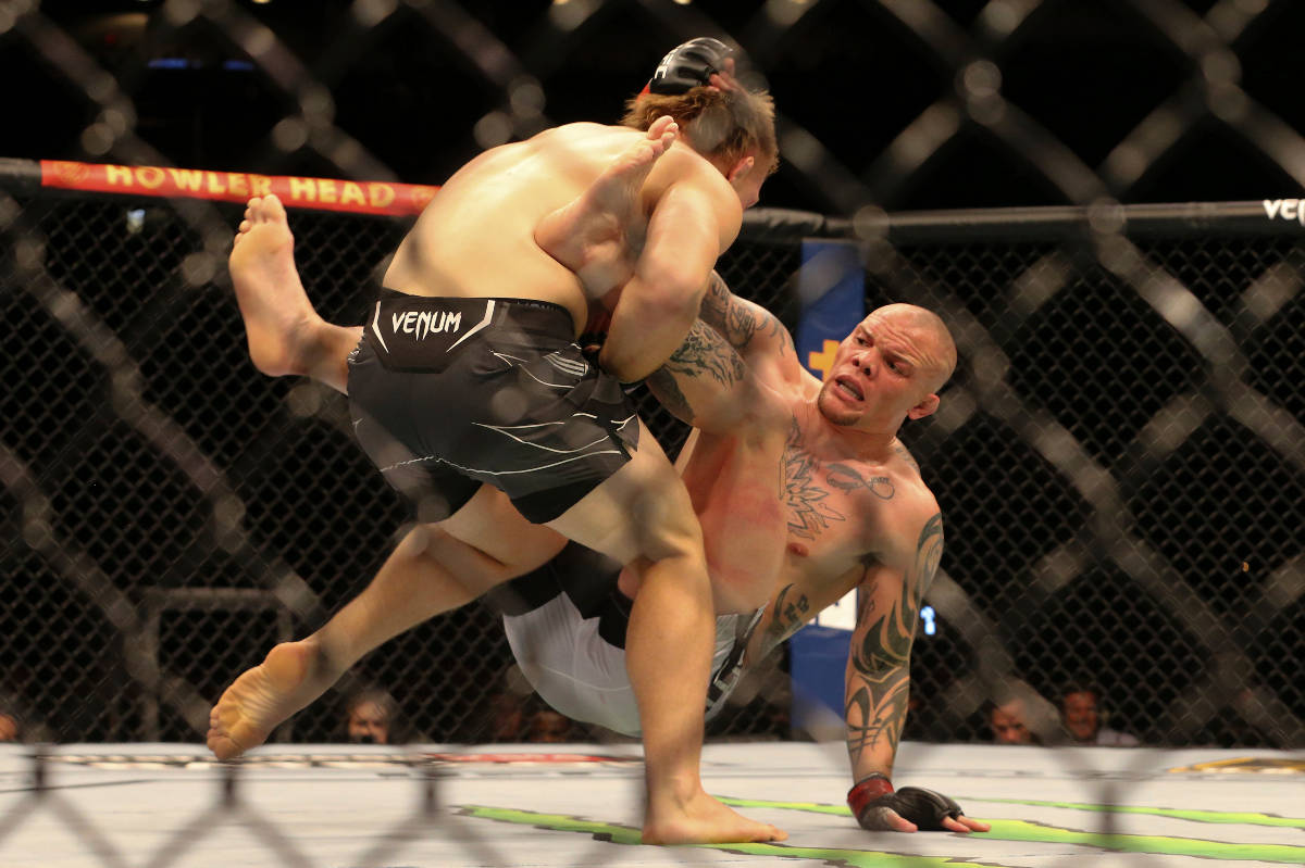 Anthony Smith, right, hits the mat while charged by Jimmy Crute during a UFC 261 mixed martial ...