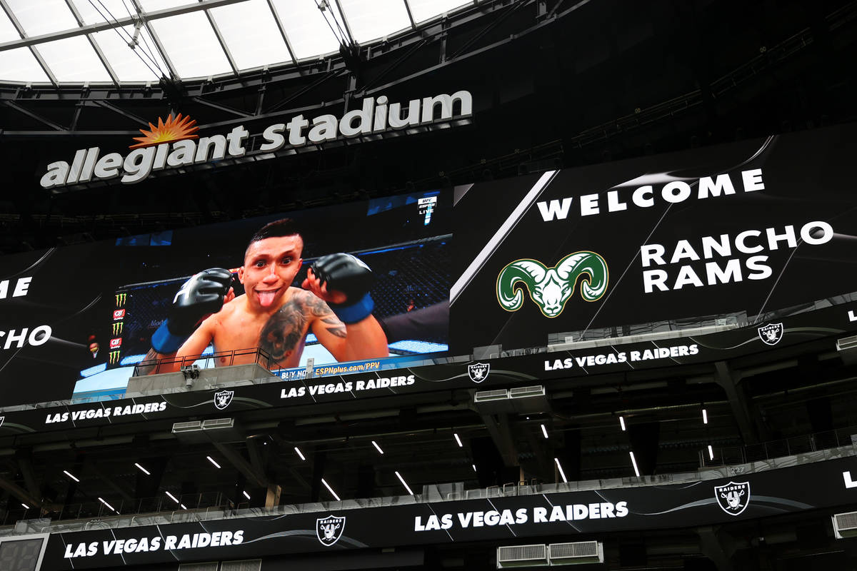 Stadium screens display a welcome message for Rancho's football team during a team practice at ...