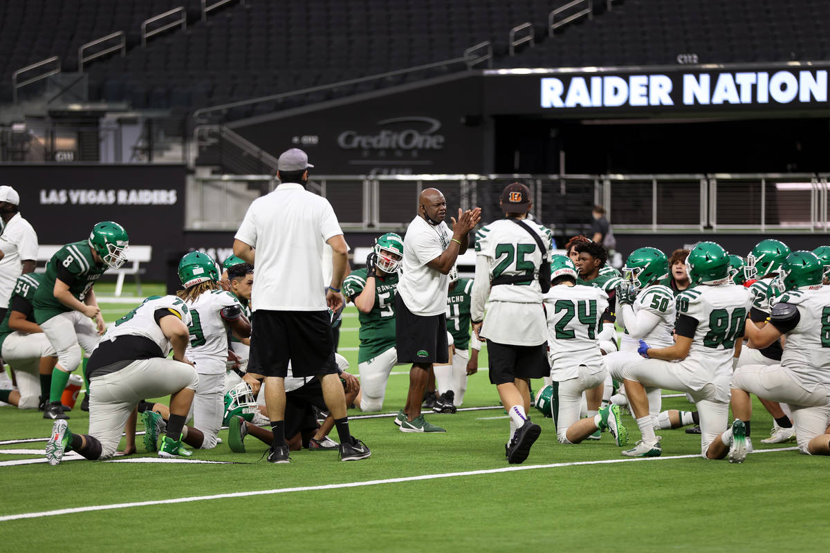 Rancho head coach Leon Evans, center, talks to his team at the end of a team football practice ...