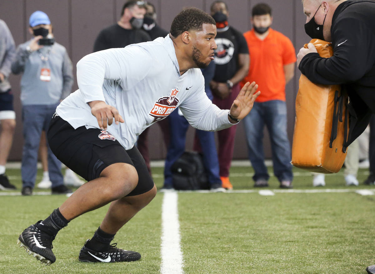 In this March 26, 2021, file photo, Christian Darrisaw runs a drill Virginia Tech pro day, atte ...