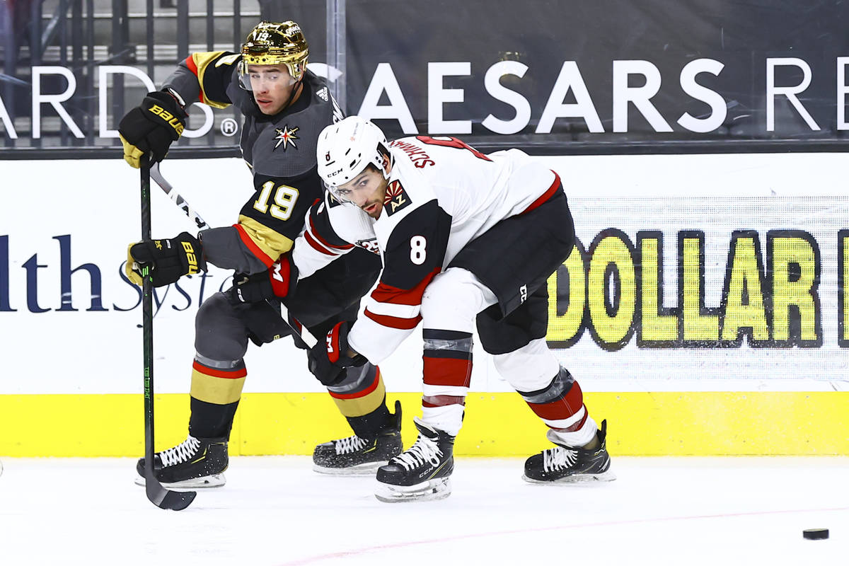 Golden Knights' Reilly Smith (19) passes the puck under pressure from Arizona Coyotes' Nick Sch ...