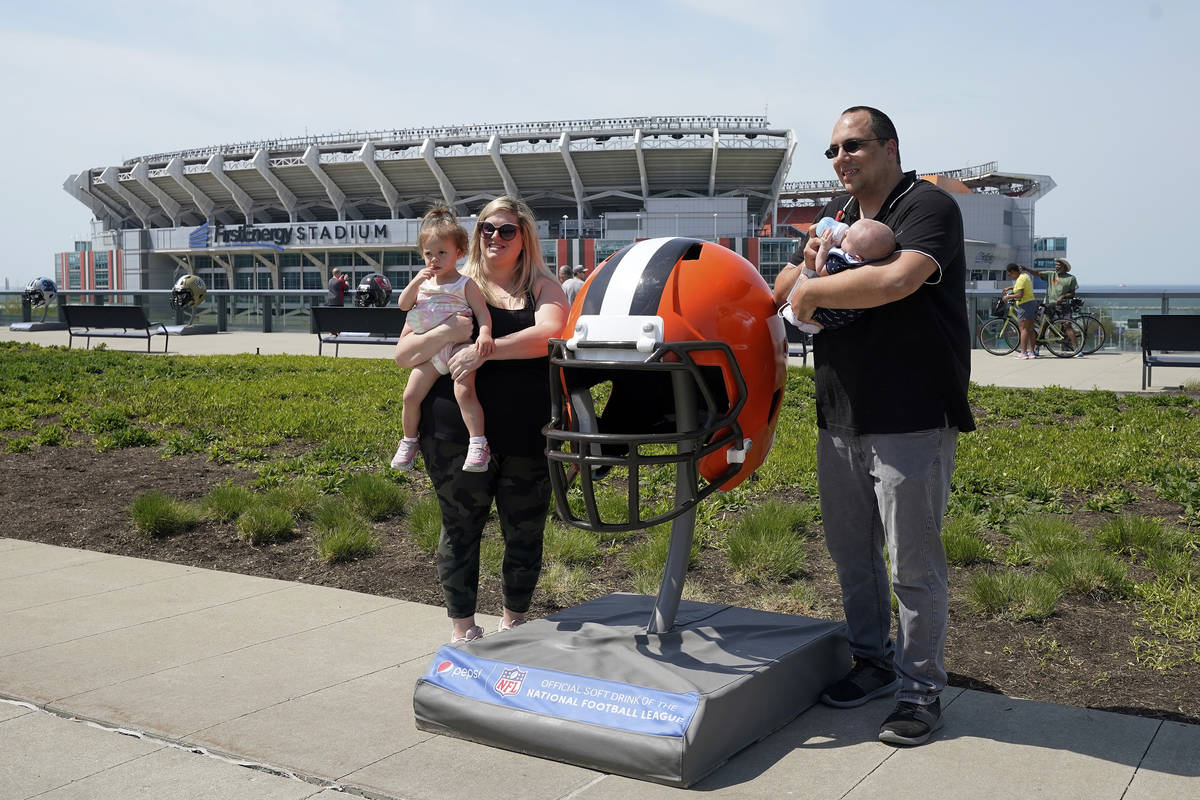 Fans pose for a photo with a large Cleveland Browns helmet, Tuesday, April 27, 2021, in Clevela ...