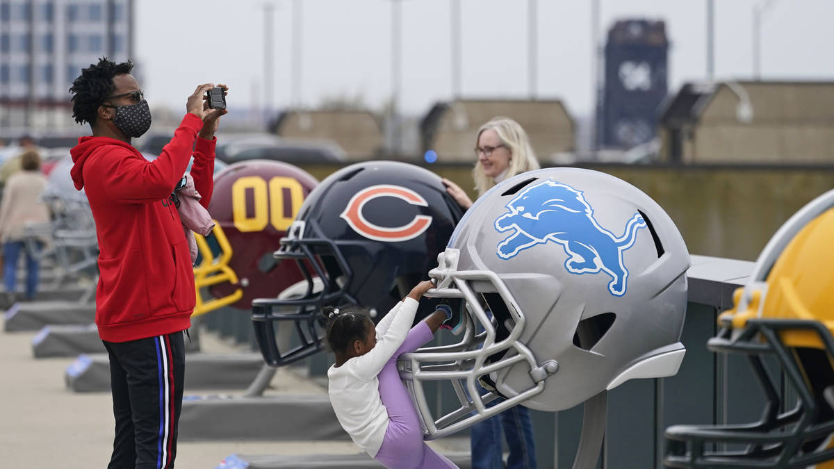 A man takes a picture where 32 teams' helmets are displayed, Saturday, April 24, 2021, in Cleve ...