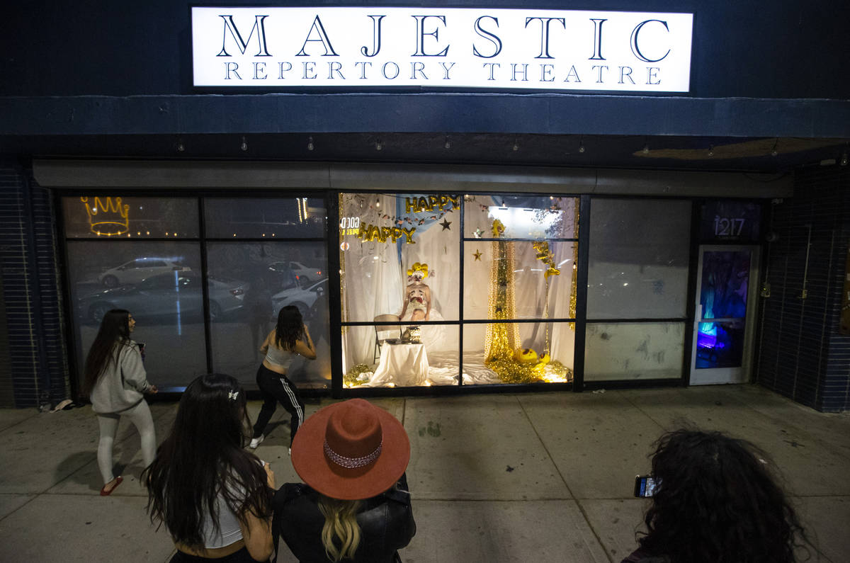 Passersby watch as Heidi Rider performs from the windows of the Majestic Repertory Theatre in t ...