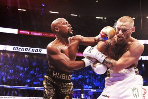 Floyd Mayweather Jr. lands a punch against Conor McGregor in the blank round on Saturday, Aug 2 ...