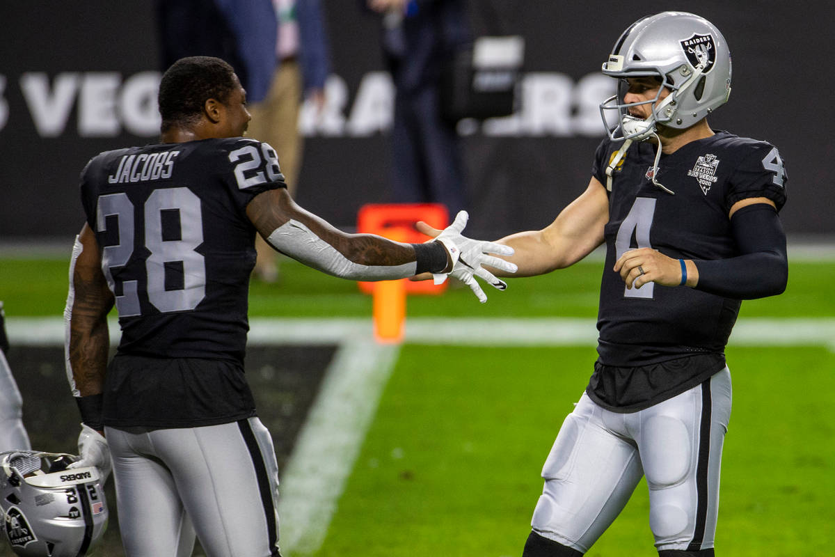 Las Vegas Raiders running back Josh Jacobs (28, left) greets quarterback Derek Carr (4) during ...
