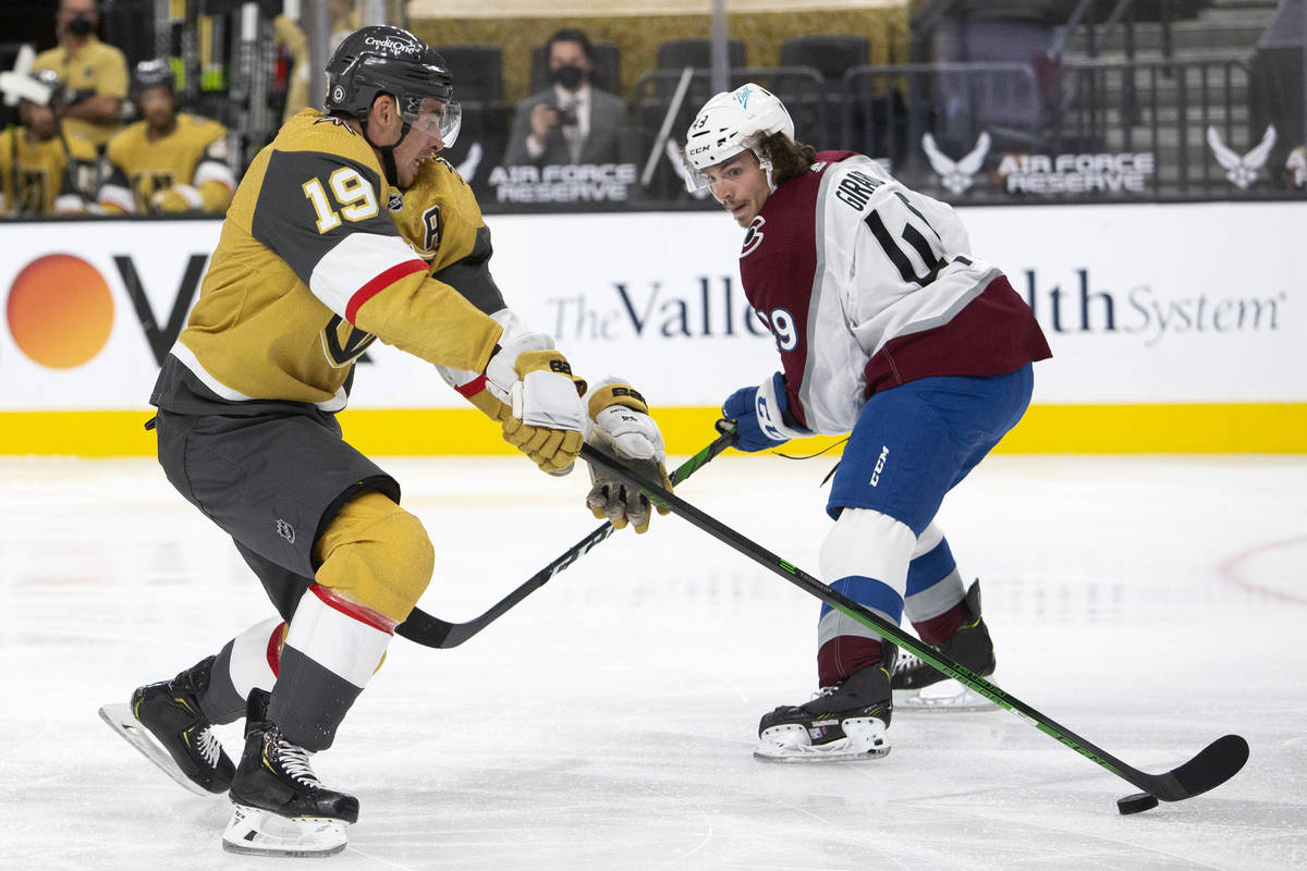Golden Knights right wing Reilly Smith (19) competes for the puck with Avalanche defenseman Sam ...