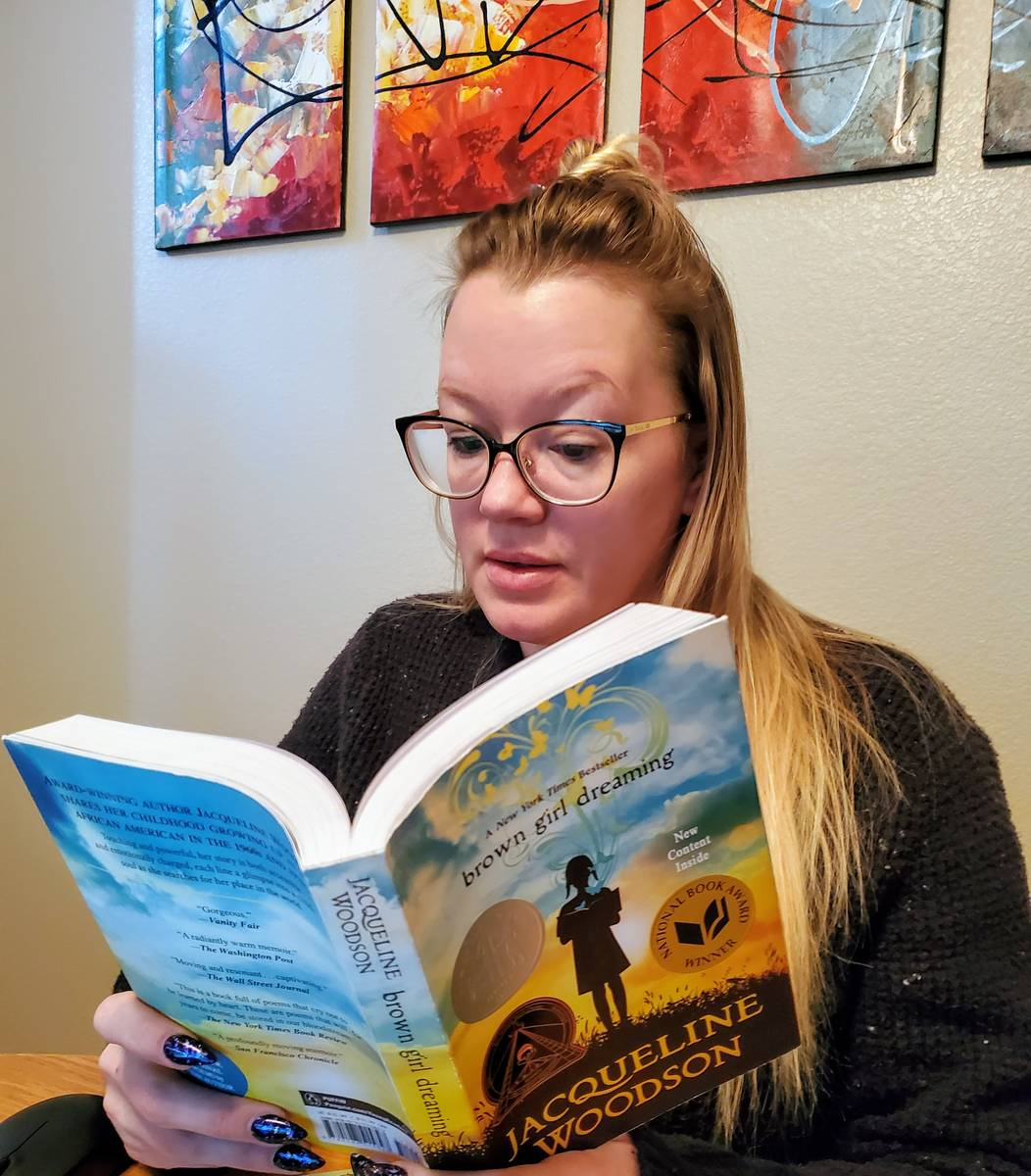 Ashley Price, a teacher at Monaco Middle School in Las Vegas, reads one of the books she reques ...