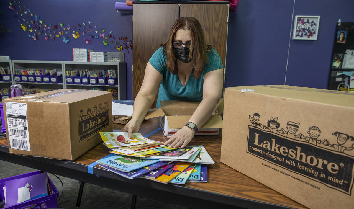 Long STEAM Academy teacher Shana Prue just received boxes of school supplies and unpacks them i ...