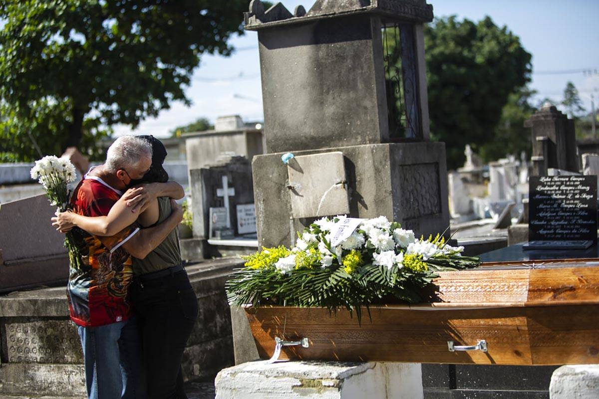 Relatives grieve during the burial service for Monica Cristina, 49, who died from complications ...