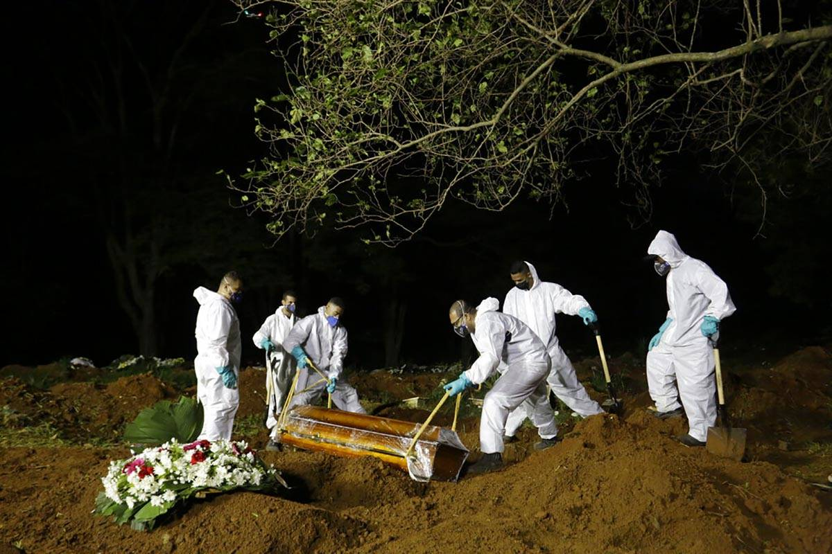 FILE - In this March 31, 2021 file photo, cemetery workers work hours past sundown, as they low ...