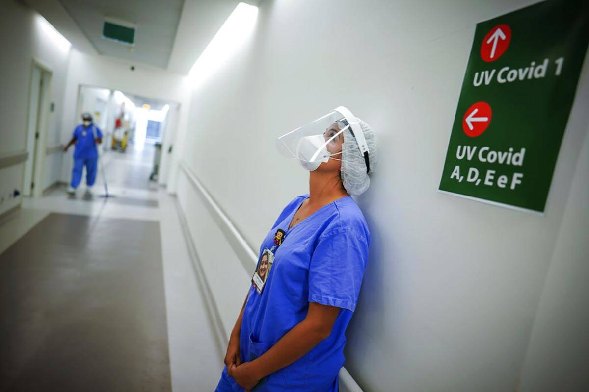 FILE - In this March 19, 2021 file photo, a healthcare worker lends against a wall in the corri ...