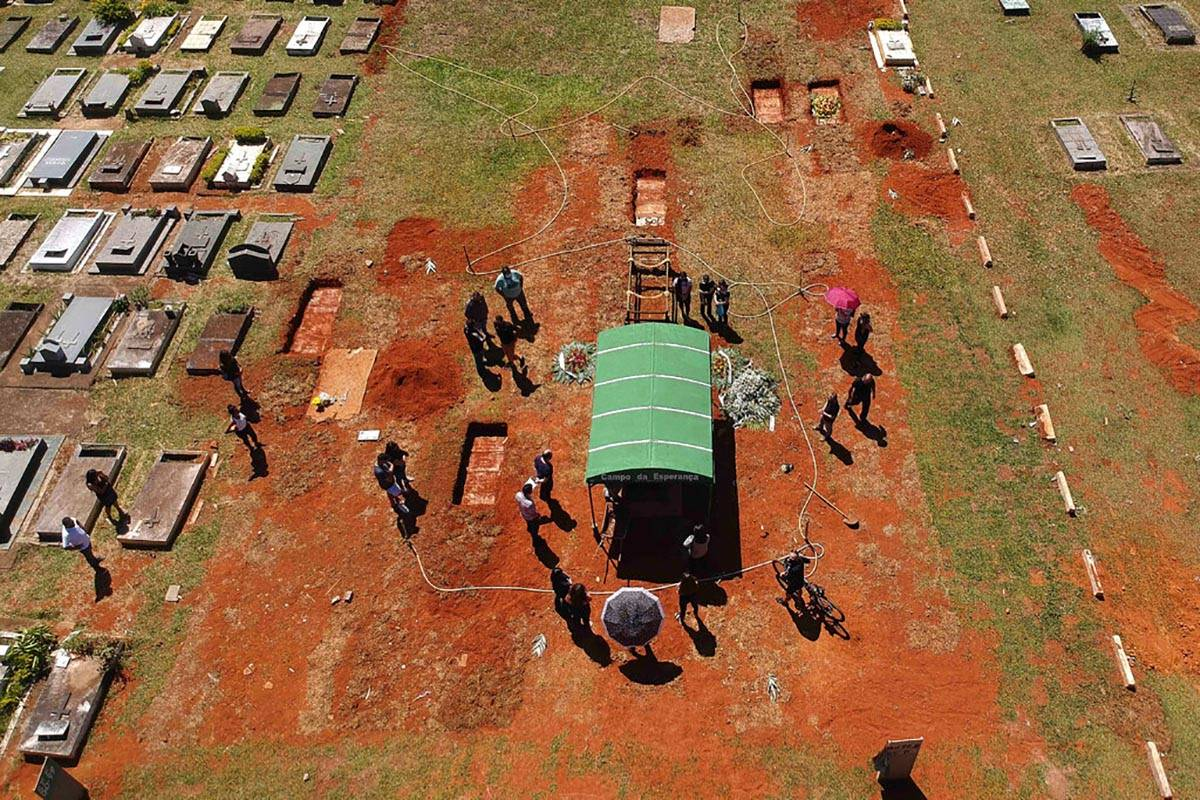 A family attends the burial service for David Ferreira Gomes, who died from complications relat ...