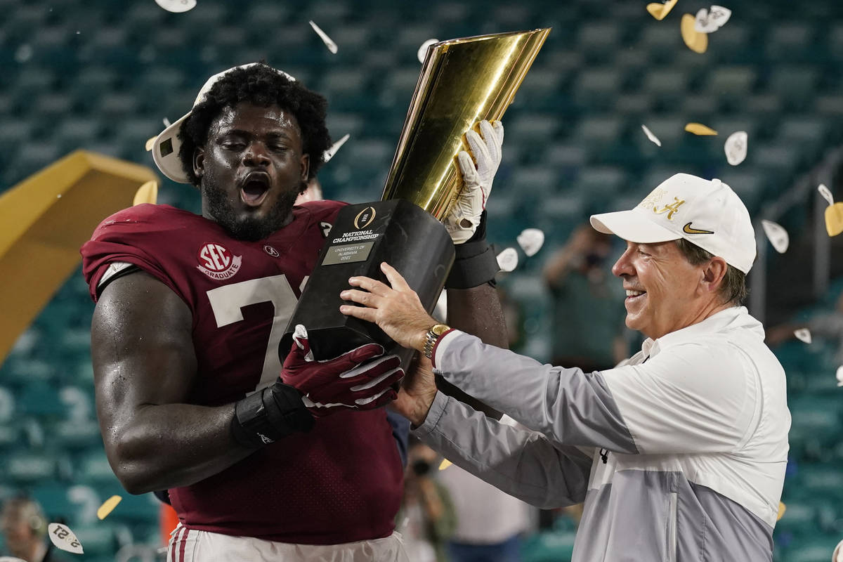 Alabama head coach Nick Saban and offensive lineman Alex Leatherwood hold the trophy after thei ...