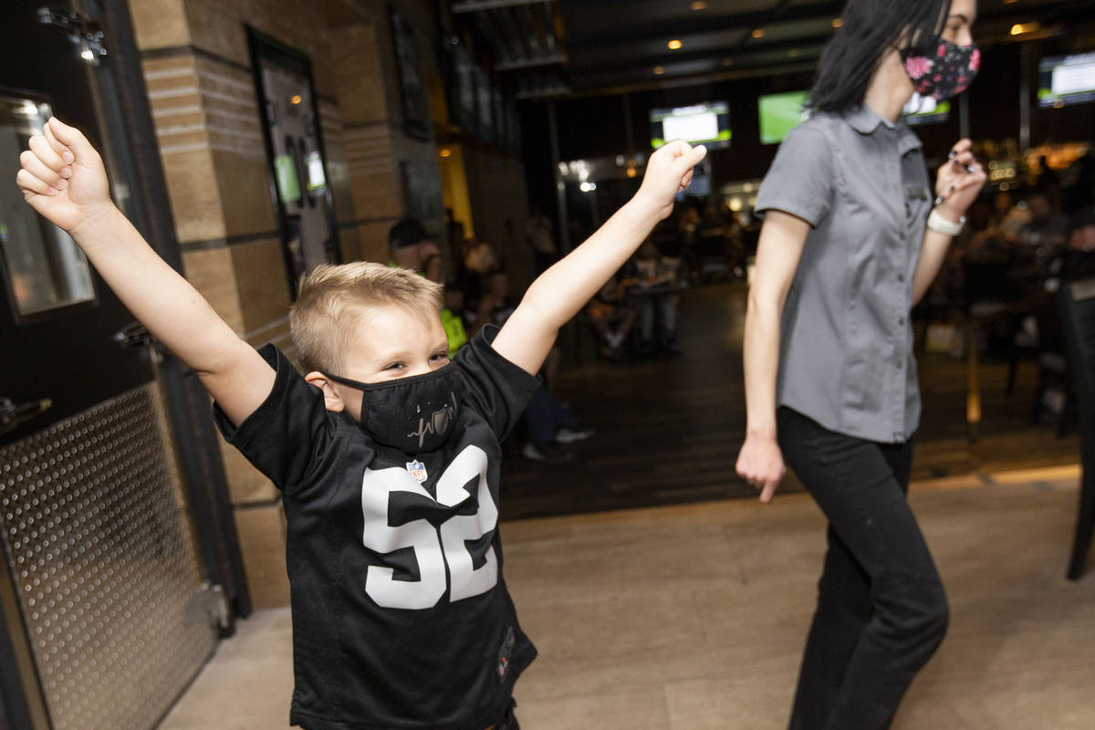 Benjamin Perks, 5, of Las Vegas, cheers right before the Raiders announced their first round NF ...