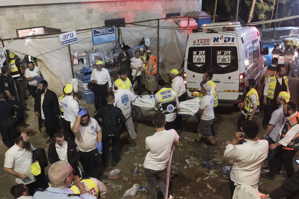 Israeli security officials and rescuers carry a body of a victim who died during a Lag Ba'Omer ...