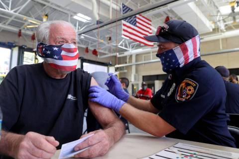 Clark County Fire Department firefighter Matt Sambol gives a COVID-19 vaccination to Don Lyon, ...