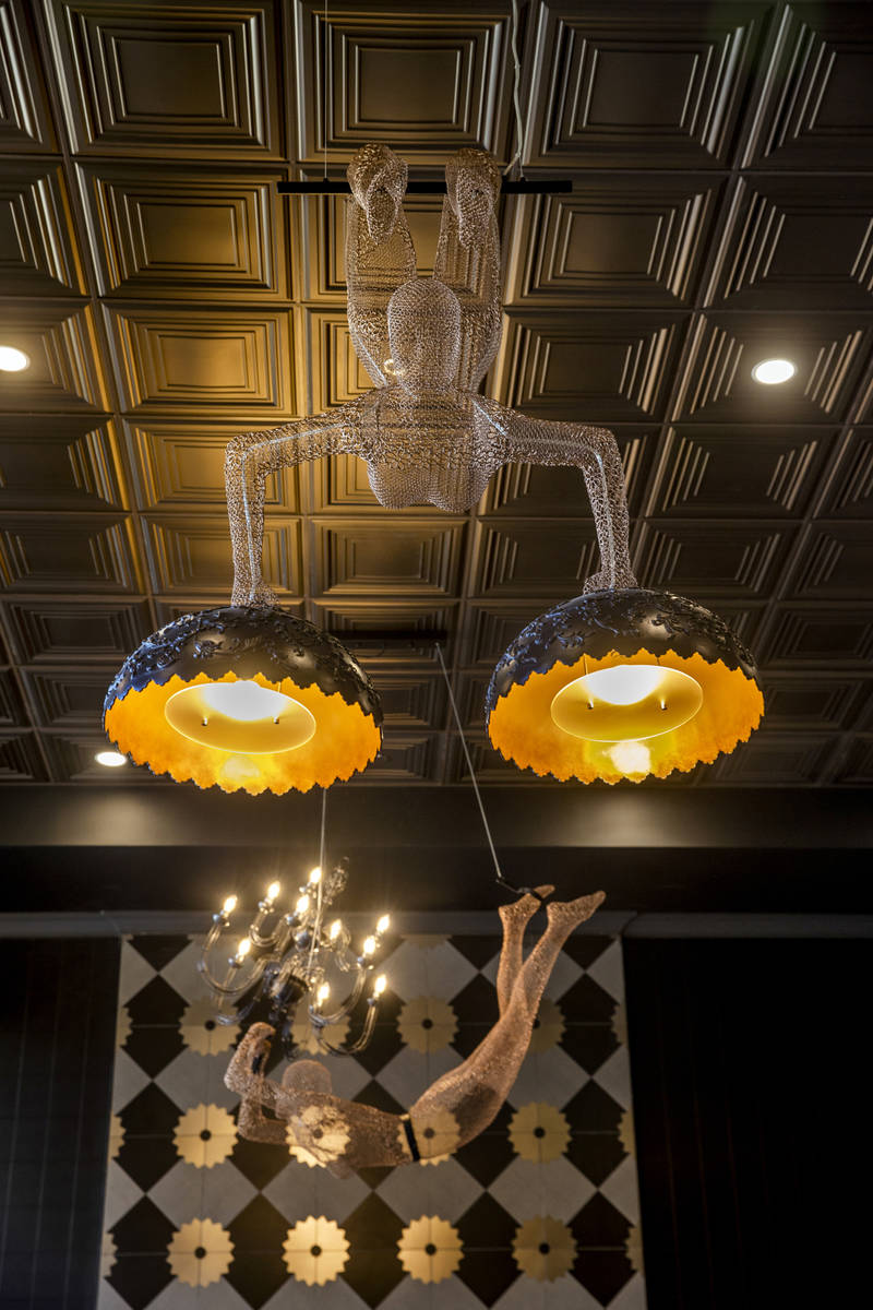 Human-figured wire lighting above the sitting area with fireplace in Elysian at Tivoli, a newly ...