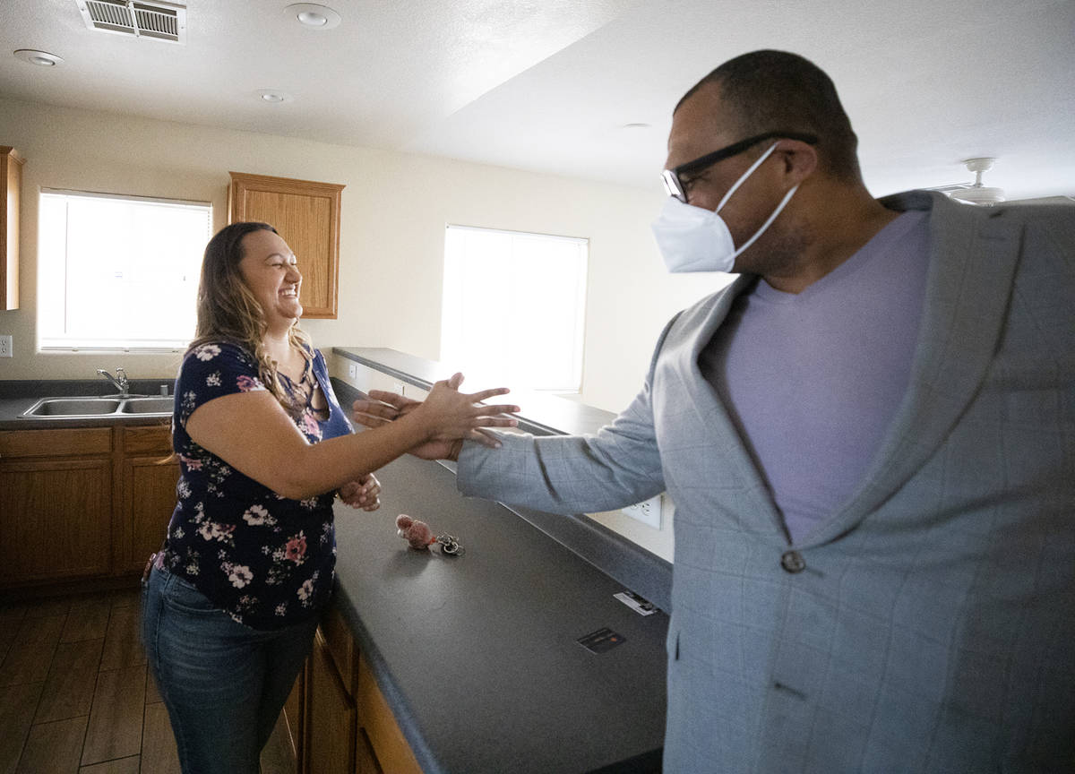 First-time homebuyer Amy Phinsee, left, fist bumps and shakes hands with realtor Cassidy Cotten ...