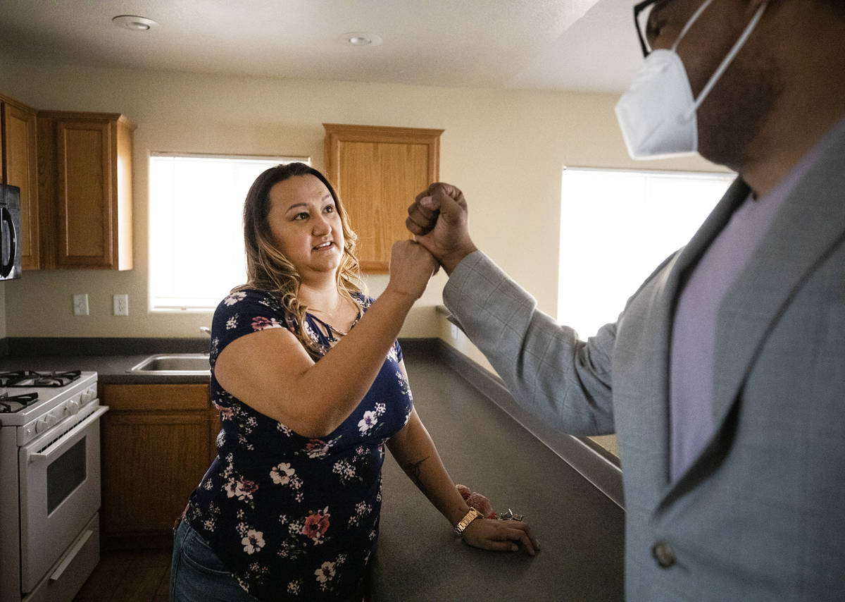 First-time homebuyer Amy Phinsee, left, fist bumps realtor Cassidy Cotten, right, at a showing ...