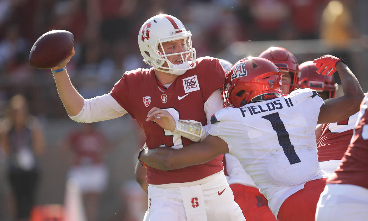 Stanford quarterback K.J. Costello, left, is pressured by Arizona's Tony Fields II (1) during t ...