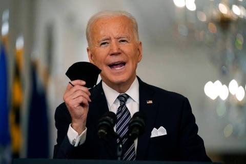 FILE - In this March 11, 2021, file photo, President Joe Biden holds up his face mask as he spe ...