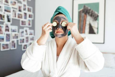 A woman puts cucumbers over her eyes as she sits up with a charcoal facial mask on her. (The Pe ...