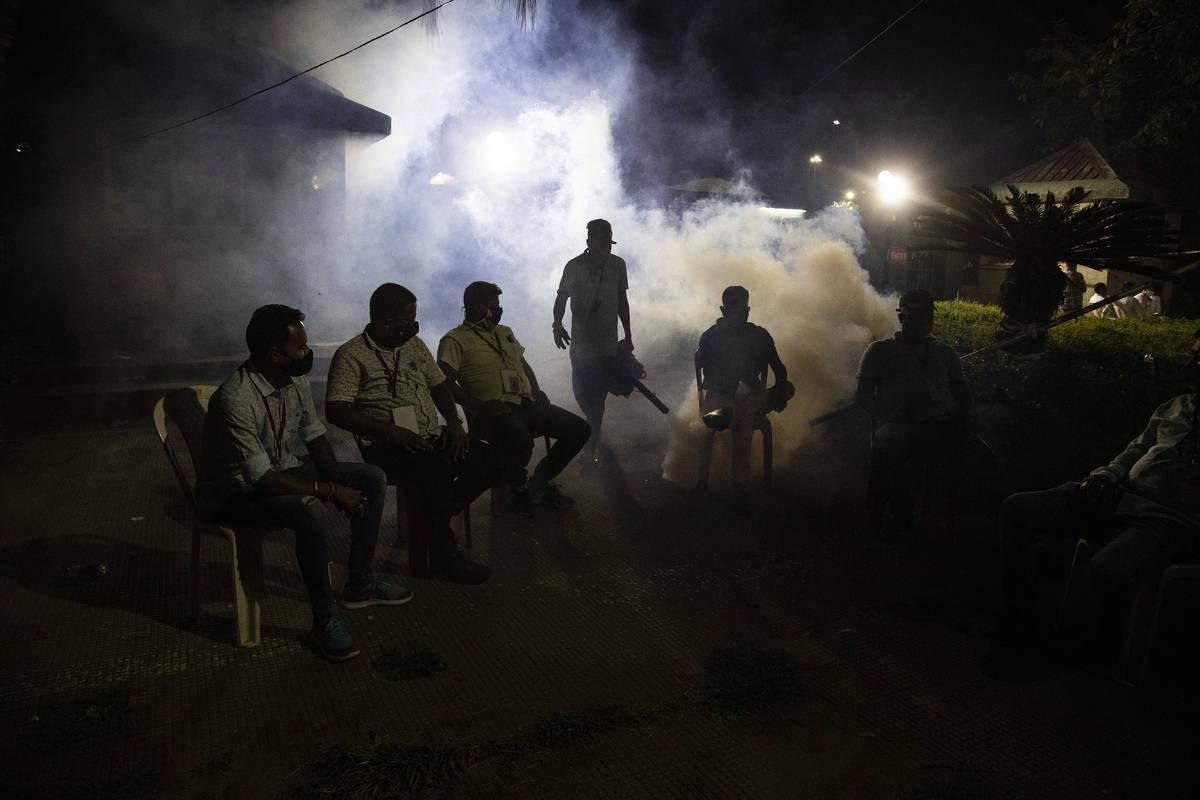 A municipal worker fumigates as supporters of Bharatiya Janata Party wait outside a vote counti ...
