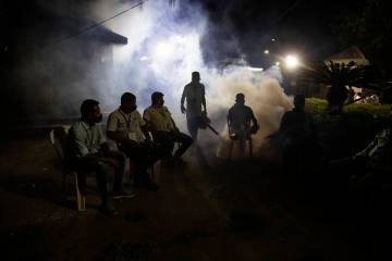 A municipal worker fumigates as supporters of Bharatiya Janata Party wait outside a vote counti ...