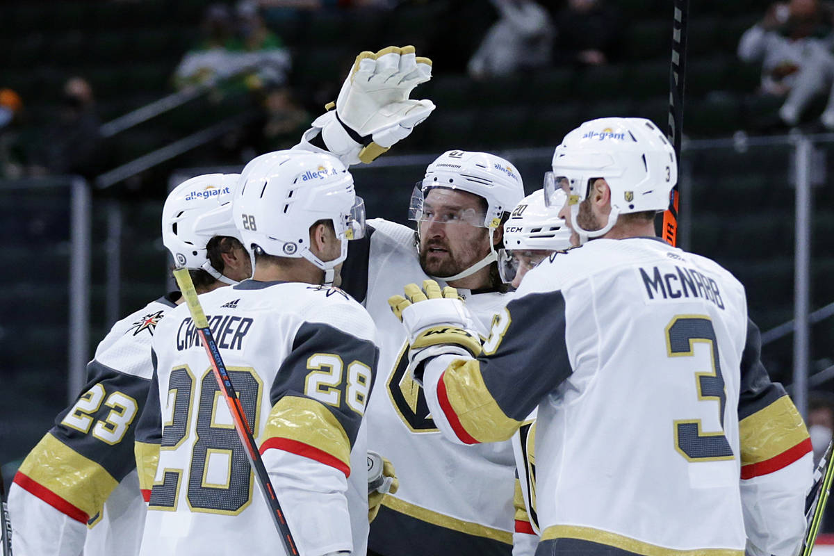 Vegas Golden Knights right wing Mark Stone (61), center, is congratulated by teammates after sc ...