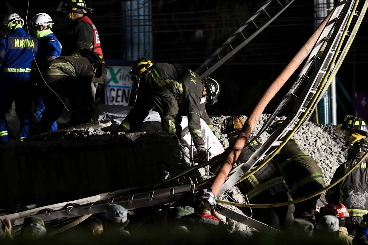 Rescue personnel retrieve bodies from the scene of an accident where subway cars fell after a s ...