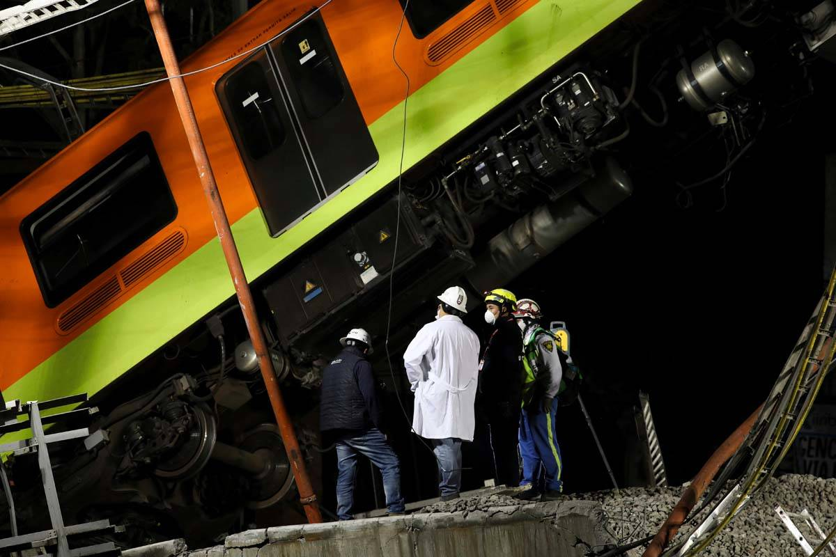 Personnel work in the rescue efforts after subway cars fell when a section of Line 12 of the su ...