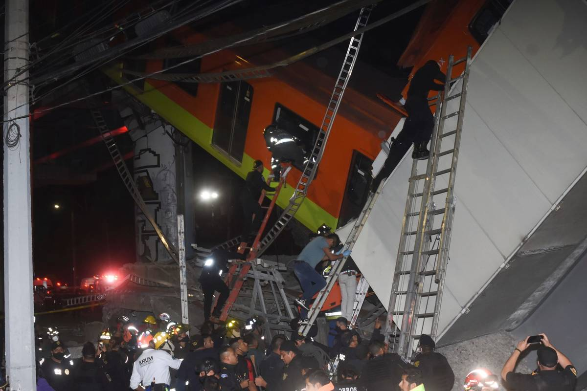 Mexico City fire fighters and rescue personnel work to recover victims from a subway car that f ...