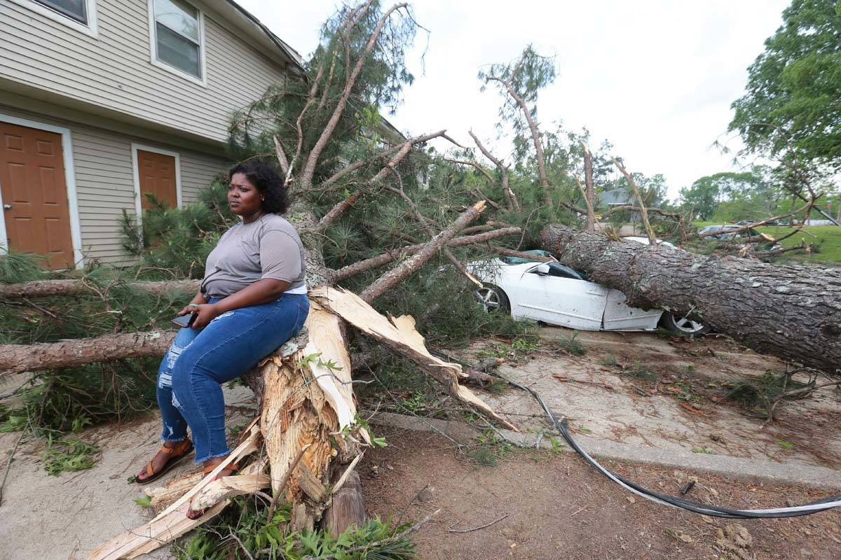 Myesha Gore of Calhoun City, Miss., sits on the trunk of a shattered pine tree Monday, May 3, 2 ...