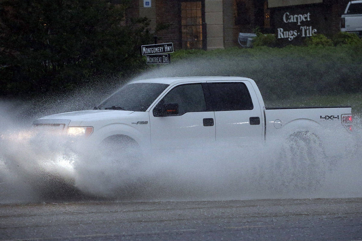 A pickup truck travels along a flooded road as severe weather produces torrential rainfall, Tue ...
