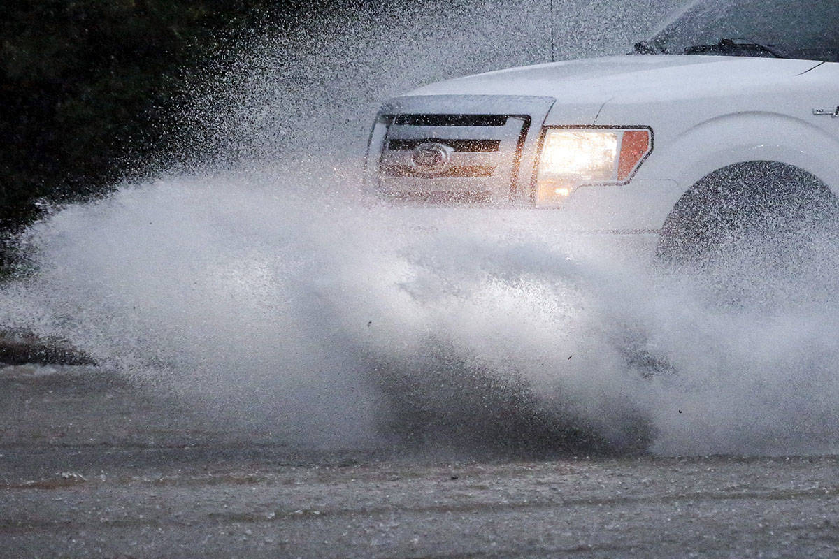 A vehicle travels along a flooded road as severe weather produces torrential rainfall, Tuesday, ...
