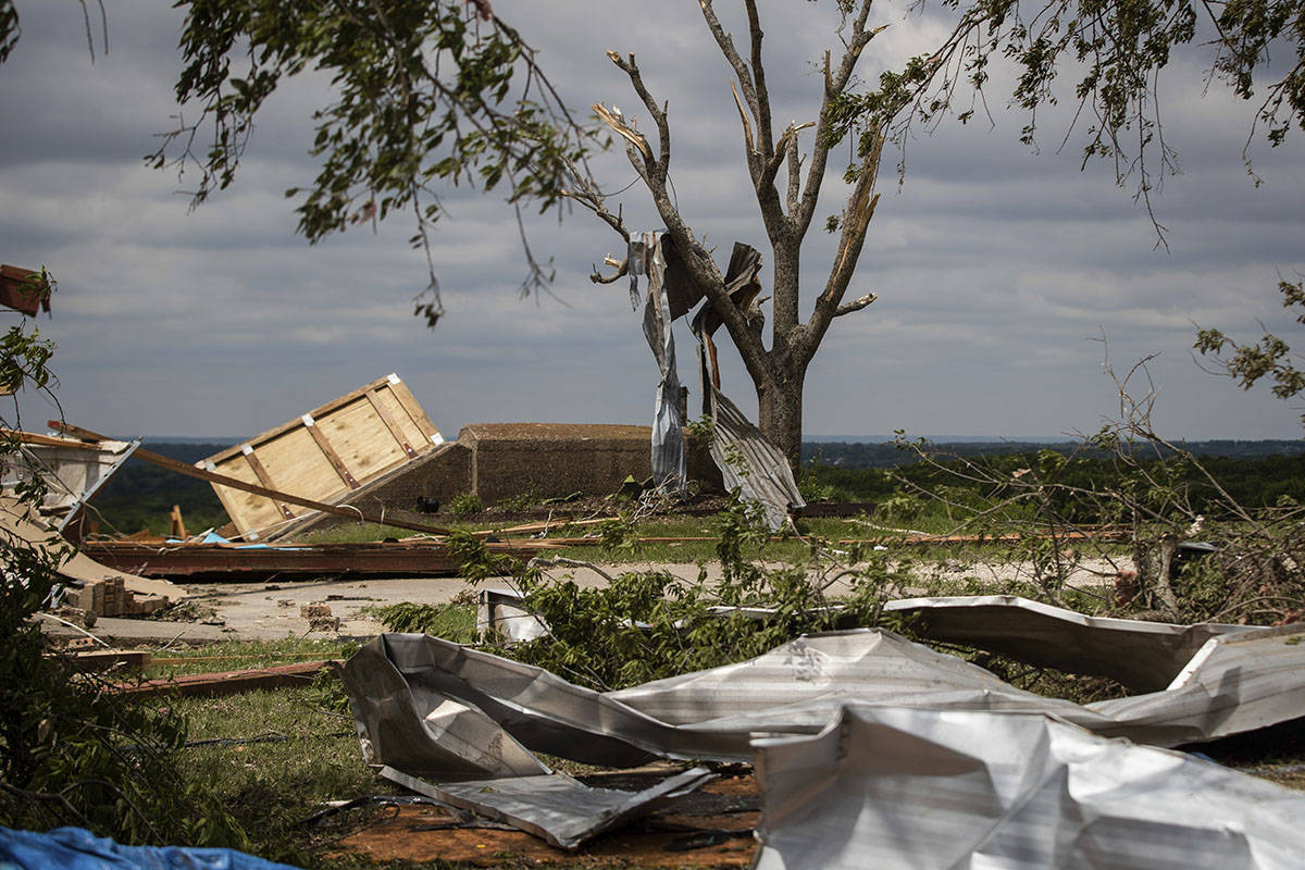 Metal parts of roof are tangled in a tree after a tornado near the storm shelter at the Barn on ...