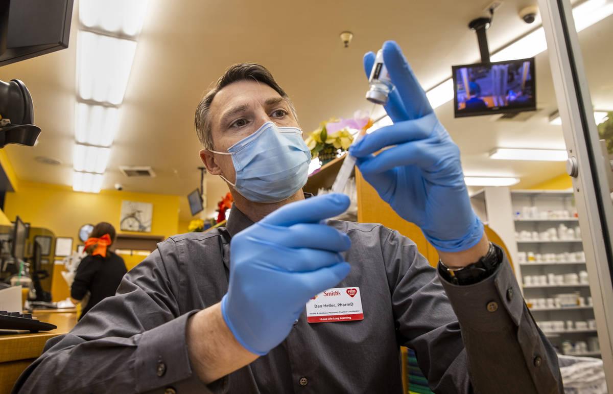 Dan Heller as the Health & Wellness Pharmacy Practice Coordinator draws up a syringe of the Mod ...