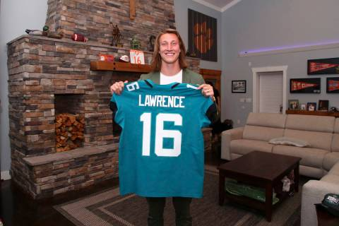 Clemson quarterback Trevor Lawrence holds up a jersey after being selected by the Jacksonville ...