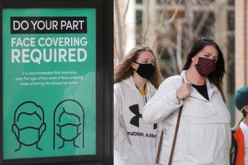A sign requiring face masks is seen at City Creek Center in Salt Lake City in March 2021. (AP P ...