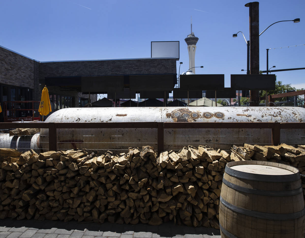 A giant BBQ smoker and smoking woods are shown at Soulbelly BBQ, Arts District BBQ spot, on Tue ...