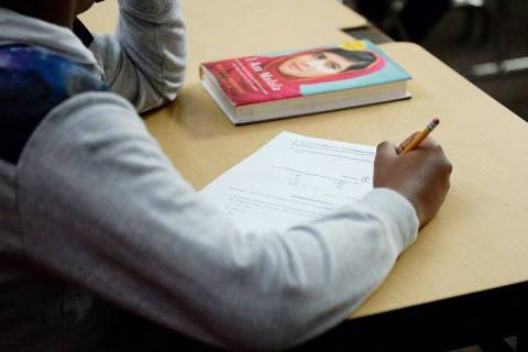 A sixth-grade student writes down math problems during class at Democracy Prep in Las Vegas, Tu ...