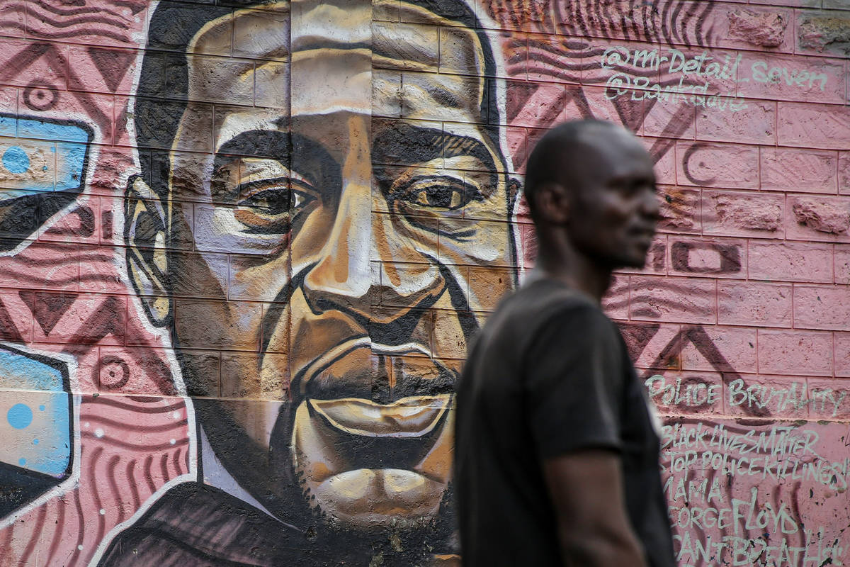A local resident stands next to a mural painted in June 2020 showing George Floyd with the Swah ...