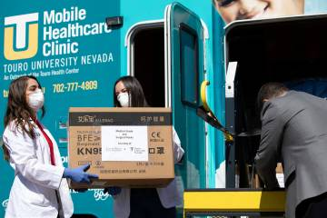 Touro University Nevada medical students help to unload at Henderson Hospital on Wednesday, Apr ...
