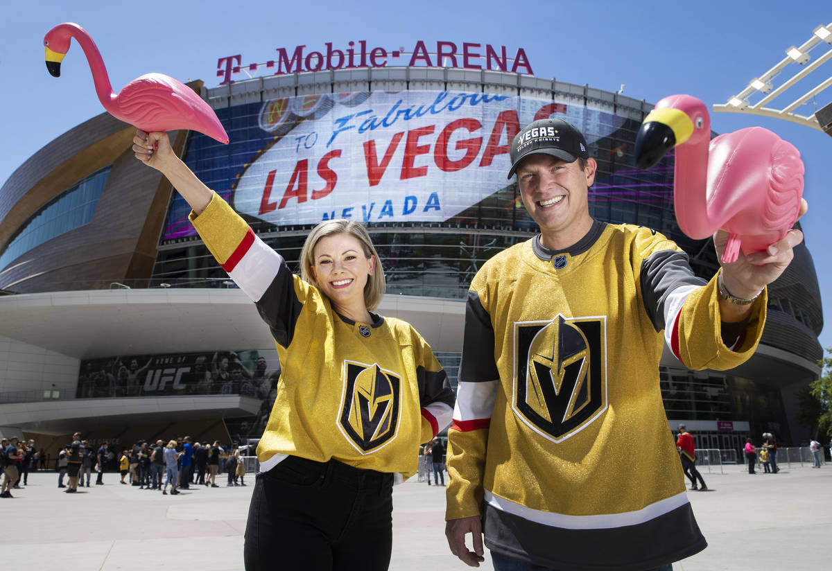 Drew Johnson, right, and wife Sarah, hold plastic flamingo's outside T-Mobile Arena on S ...