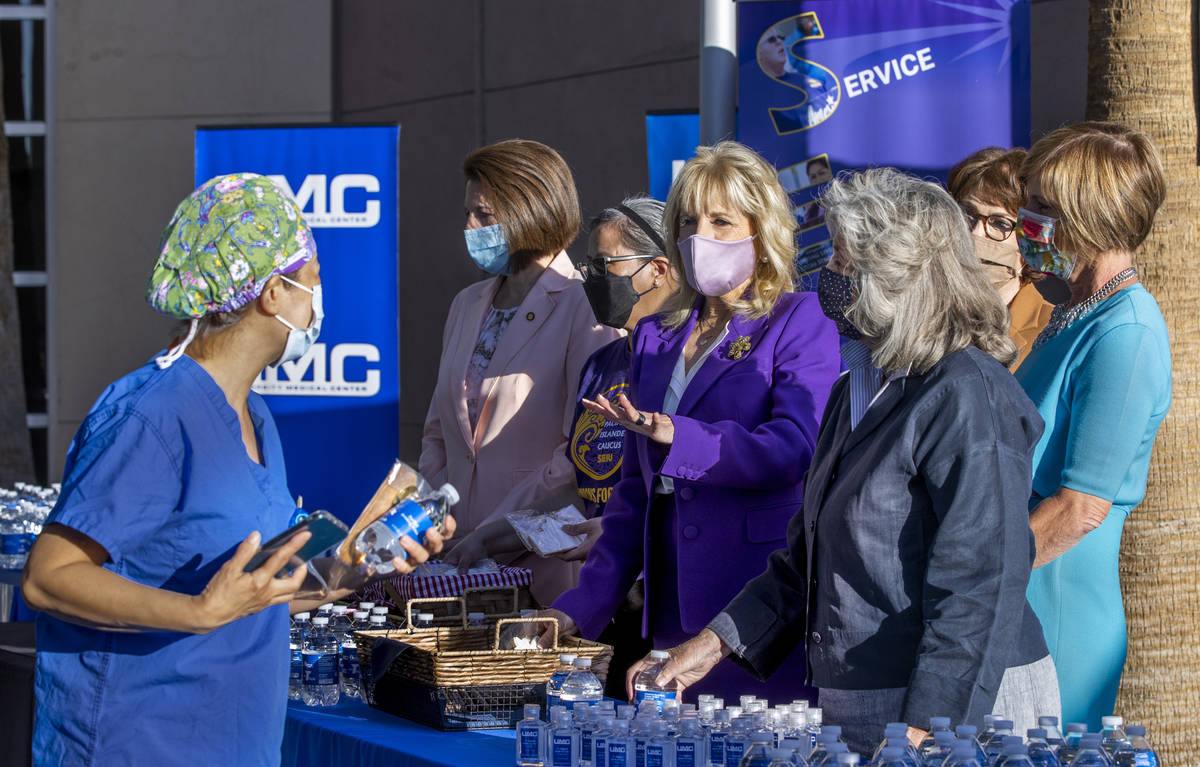 A staff person, left, chats with First Lady Jill Biden, center, and others at the University Me ...