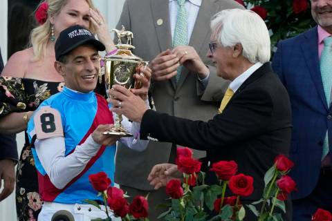 Trainer Bob Baffert hands the winner's trophy to jockey John Velazquez after they victory with ...