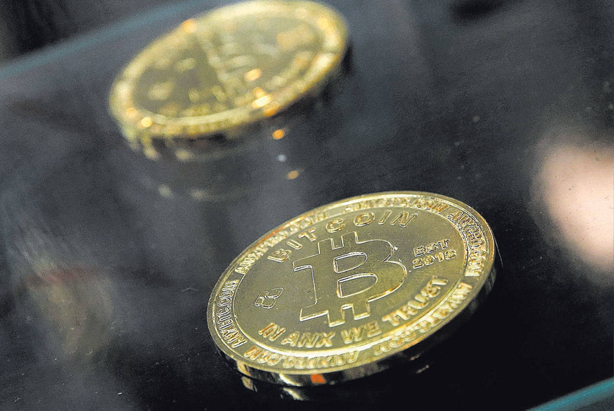 Coins are displayed next to a Bitcoin ATM in Hong Kong. (AP Photo/Kin Cheung)