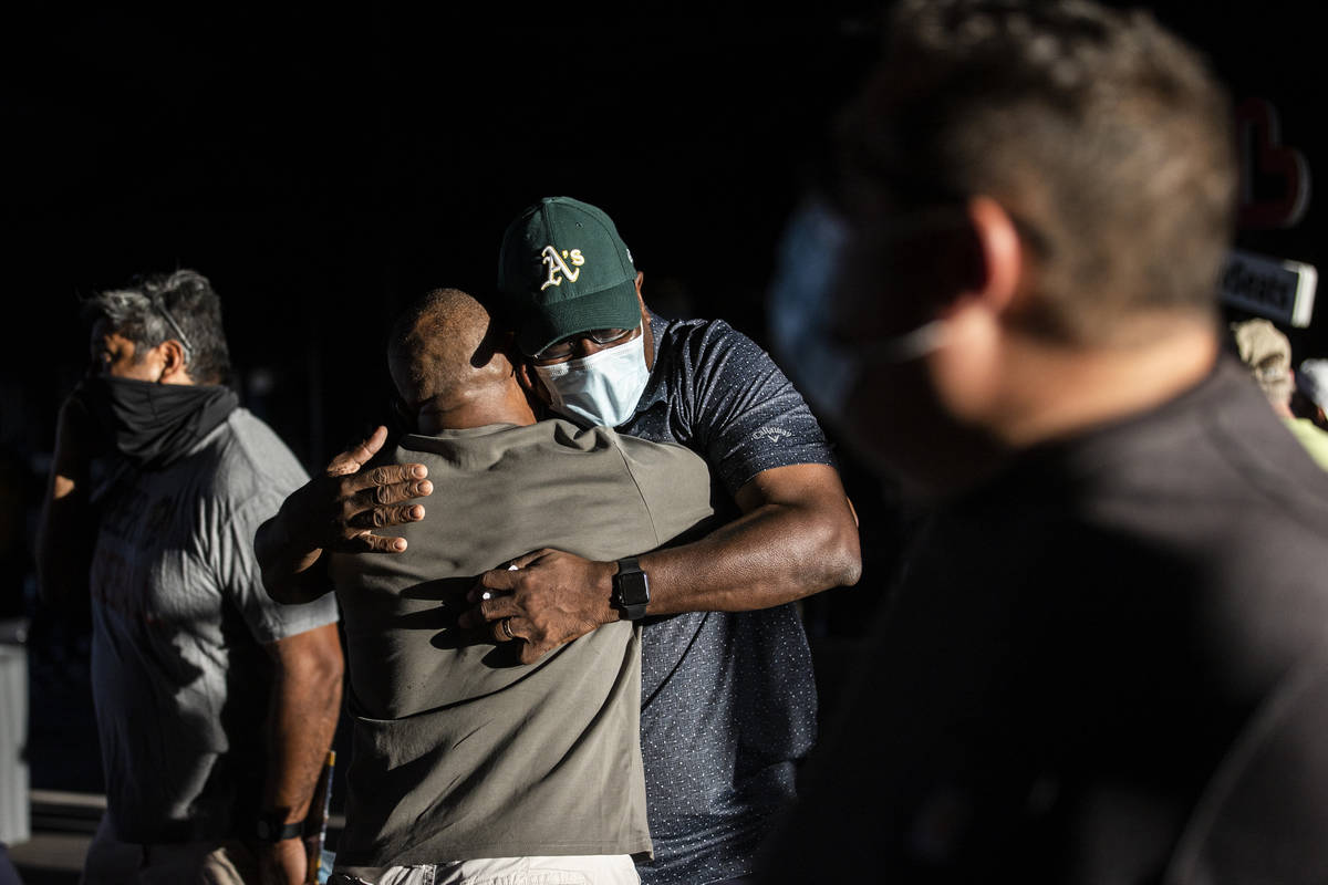 Mike Reed, facing, hugs friend John Gregory before the start of a Triple-A baseball game betwee ...