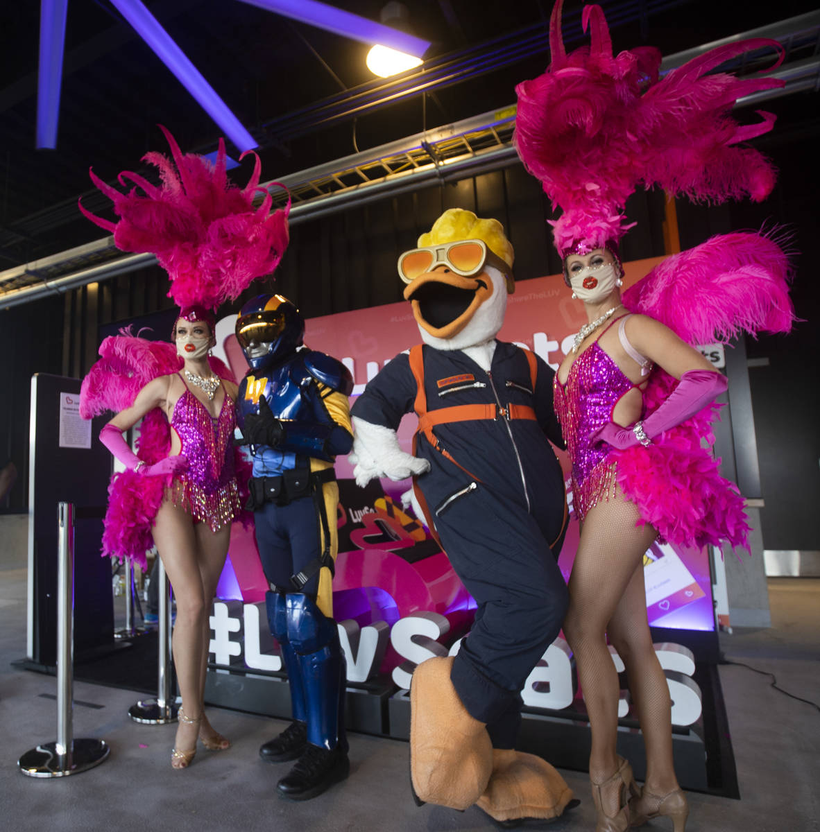 Aviator, second from left, and Spruce the Goose pose with showgirls before the start of a Tripl ...